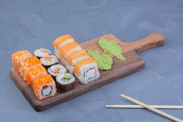 Filadélfia, salmão e saquê maki rolos com wasabi em uma travessa de madeira.