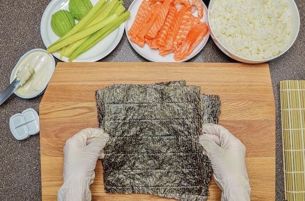 Filadélfia sushi maki e ingredientes, em uma tábua de madeira, vista superior, copie o espaço na folha de nori.