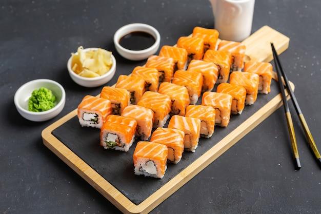 Filadélfia sushi roll feito de salmão fresco, abacate e cream cheese no interior. cozinha tradicional japonesa