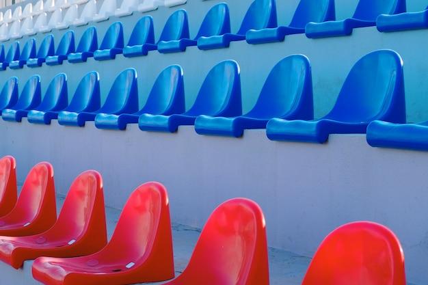 Filas de assentos em vermelho, azul e branco para espectadores nas arquibancadas do estádio