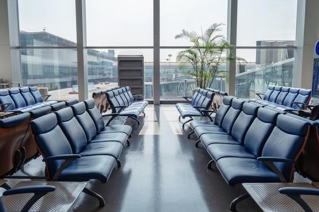 Filas de cadeira com janelas de vidro brilham no terminal no aeroporto