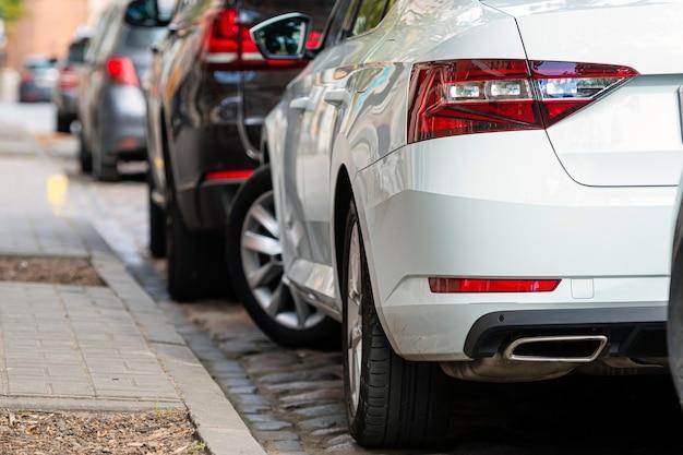 Filas de diferentes carros estacionados ao longo da estrada em uma cidade movimentada