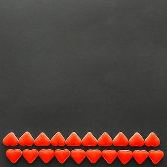 Filas de doces de forma de coração vermelho no fundo do pano de fundo preto