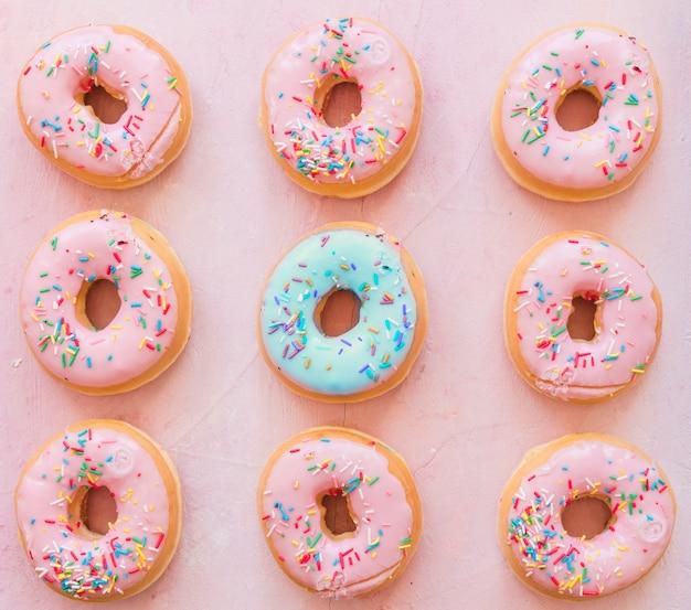 Filas de donuts no fundo rosa