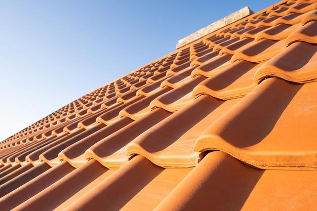 Filas sobrepostas de telhas de cerâmica amarela cobrindo o telhado de edifícios residenciais.