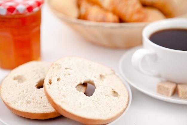 Filé cortado ao meio e uma xícara de café em pratos brancos com açúcar e leite e uma panela de geléia