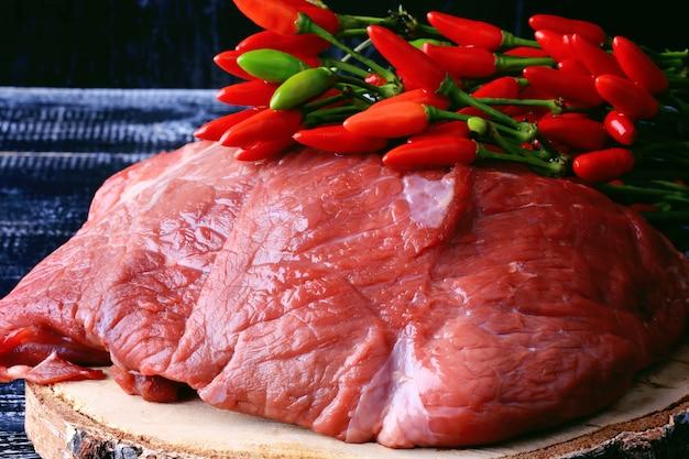 Filé cru de carne com pimenta no estilo retrô de superfície de madeira escura