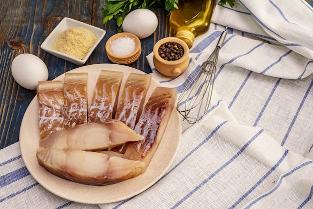 Filé cru de salsicha e ingredientes para fritar. fatias frescas em um prato, temperos, ovos, óleo, farinha de rosca, salsa