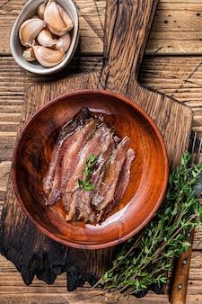 Filé de anchovas em conserva em uma tigela de madeira. fundo de madeira. vista do topo.