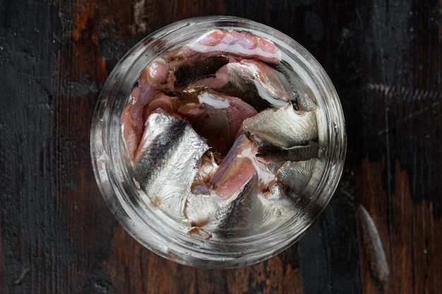 Filé de anchovas salgadas em conserva, em frasco de vidro, na velha mesa de madeira escura