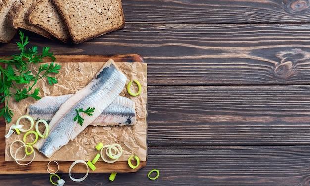 Filé de arenque com salsa e cebola em uma placa de corte, vista superior, fundo escuro de madeira. ingredientes smorrebrod noruegueses ou dinamarqueses tradicionais. sanduíche de arenque, conceito de comida saudável.