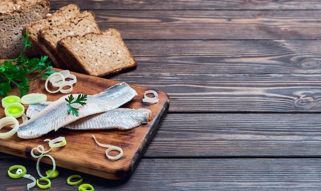 Filé de arenque com salsa e cebola em uma tábua, mesa de madeira escura com lugar para texto. ingredientes smorrebrod noruegueses ou dinamarqueses tradicionais. sanduíche de arenque, conceito de comida saudável.