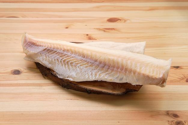 Filé de bacalhau congelado na mesa de madeira