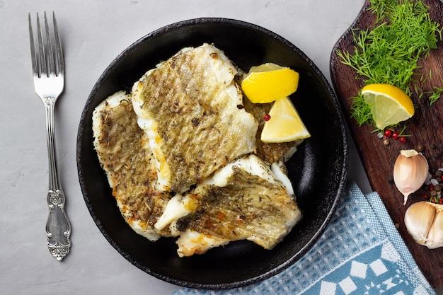 Filé de bacalhau frito com especiarias em uma panela de ferro fundido. vista do topo.