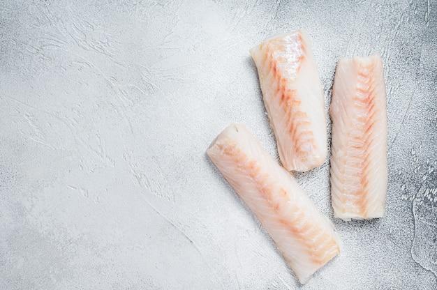 Filé de bacalhau norueguês cru na mesa da cozinha. fundo branco. vista do topo. copie o espaço.