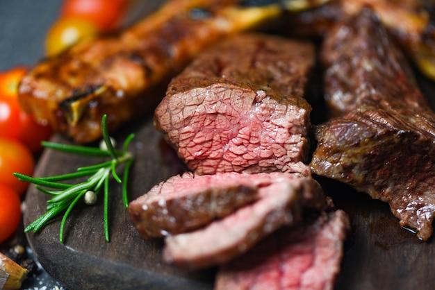 Filé de bife assado com ervas e especiarias, servido com vegetais na placa de madeira - fatia de carne grelhada em fundo preto