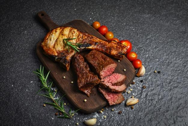 Filé de bife assado e costeletas de porco com ervas e especiarias servem com legumes na tábua de madeira - fatia de carne de bovino grelhada em fundo preto