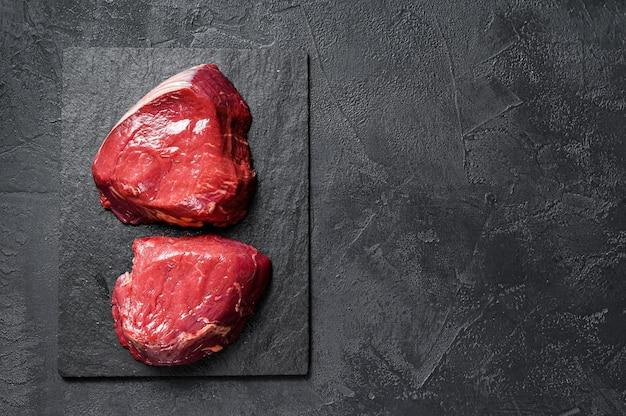 Filé de bife cru mignon preparado para cozinhar. lombinho de carne. fundo preto. vista do topo. espaço para texto