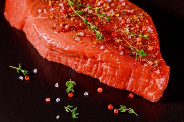 Filé de carne crua com ervas, sal e pimenta sobre placa de pedra preta.