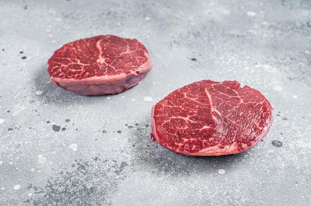 Filé de carne crua mignon bifes em uma placa de açougueiro. plano de fundo cinza. vista do topo.