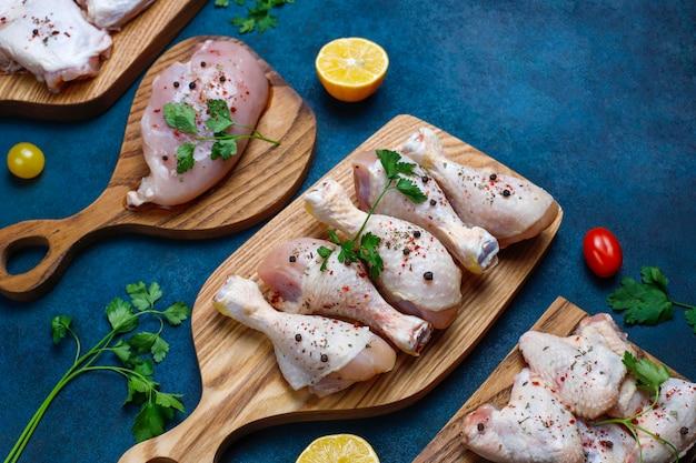 Filé de carne de frango cru, coxa, asas e pernas com ervas, especiarias, limão e alho em fundo azul escuro. vista do topo