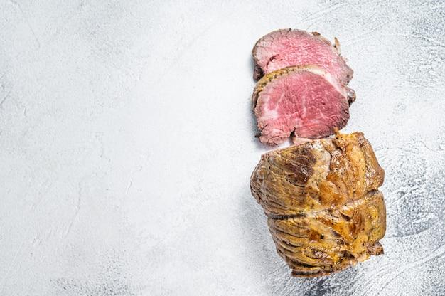 Filé de carne de rosbife na mesa da cozinha. fundo branco. vista do topo. copie o espaço.