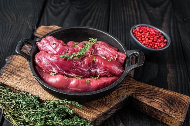 Filé de carneiro cru filé carne, lombo de borrego em frigideira rústica com tomilho. fundo de madeira preto. vista do topo.