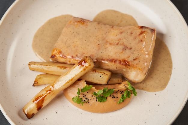 Filé de esturjão cozido com espinafre em um prato branco na mesa cinza
