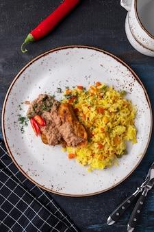 Filé de frango assado e arroz com legumes em um prato. vista do topo