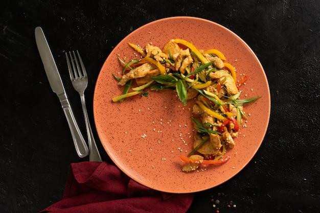 Filé de frango com legumes, pimenta e cebola. prato com frango em uma mesa preta. vista do topo.