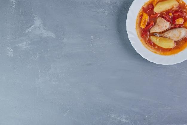 Filé de frango com molho de tomate em um prato branco.