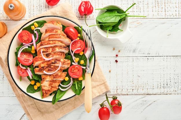 Filé de frango com salada de espinafre, tomate cereja, centáurea e cebola. comida saudável. dieta ceto, conceito de almoço de dieta. vista superior em fundo branco.