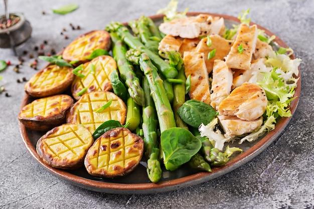 Filé de frango cozido em uma grelha com um enfeite de aspargos e batatas assadas. cardápio dietético. comida saudável.