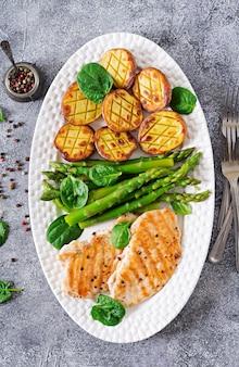 Filé de frango cozido em uma grelha com um enfeite de aspargos e batatas assadas. menu dietético. comida saudável. postura plana. vista do topo