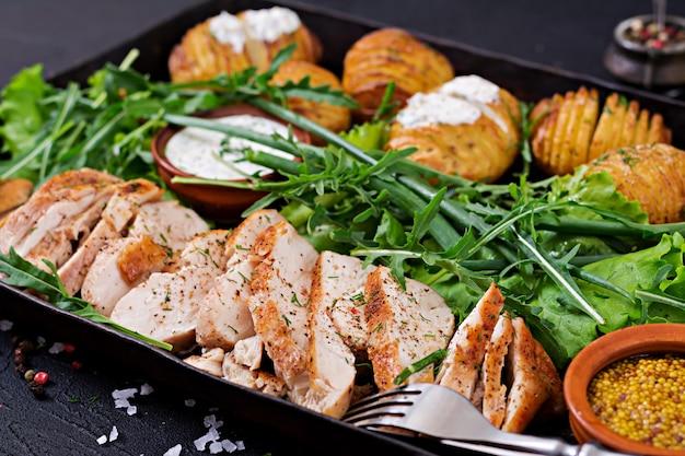 Filé de frango cozido em uma grelha com um enfeite de batatas assadas. refeição dietética. comida saudável.