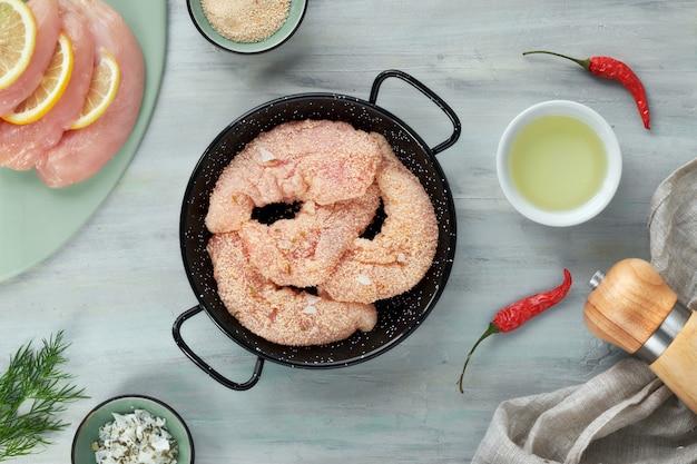 Filé de frango cru. carne com farinha de rosca, ervas, limão e óleo de cozinha