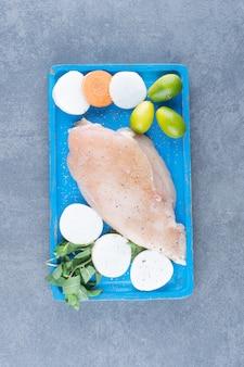 Filé de frango cru com legumes frescos no quadro azul.