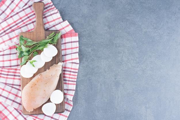 Filé de frango cru com rodelas de rabanete na placa de madeira.