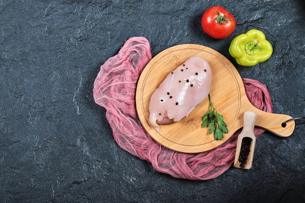 Filé de frango cru na placa de madeira com legumes e toalha de mesa.