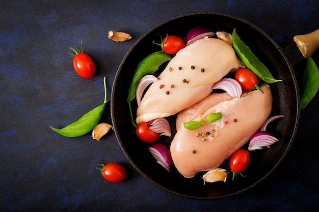 Filé de frango cru preparado para assar em uma panela sobre uma mesa escura. vista do topo