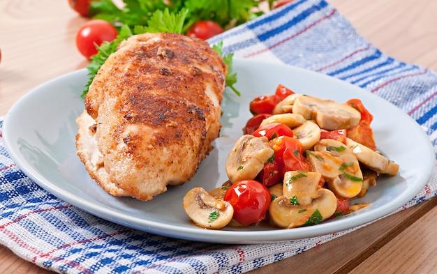 Filé de frango em farinha de rosca crocante, guarnecido com cogumelos e tomates