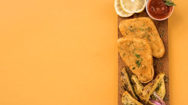 Filé de frango empanado e fatias de batata na tábua de madeira