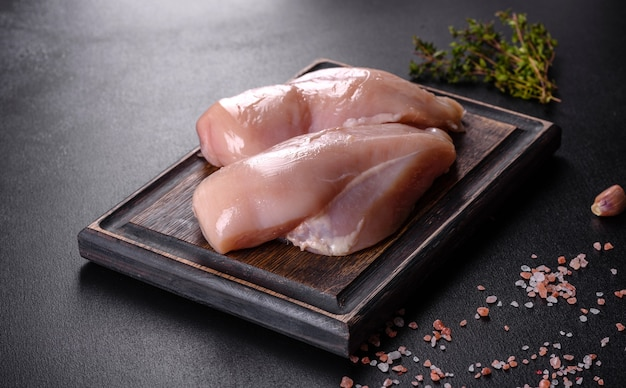 Filé de frango fresco em uma mesa de concreto escura com especiarias e ervas. preparação para cozinhar pratos de carne