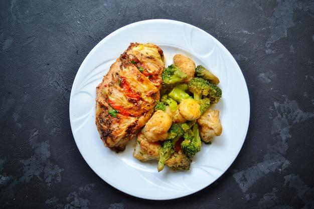 Filé de frango frito. brócolis e couve-flor. peito de frango assado. frango e tomate. comida em um prato branco sobre uma mesa de concreto preta.