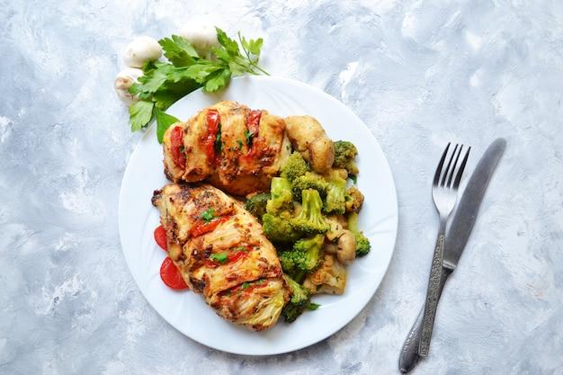 Filé de frango frito. brócolis e couve-flor. peito de frango assado. frango e tomate. comida em um prato branco sobre uma mesa de luz