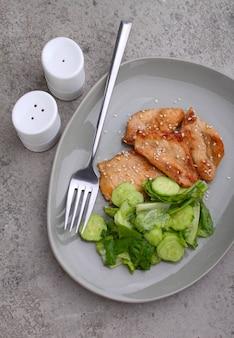 Filé de frango frito em molho de soja em um prato decorado com sementes de gergelim e salada verde, vista superior.