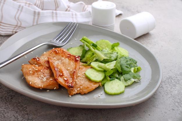 Filé de frango frito em molho de soja em um prato decorado com sementes de gergelim e salada verde.