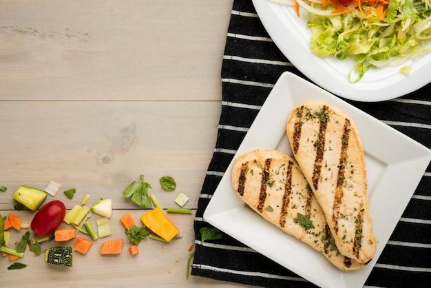 Filé de frango grelhado com salada e pedaços de vegetais espalhados na mesa de madeira