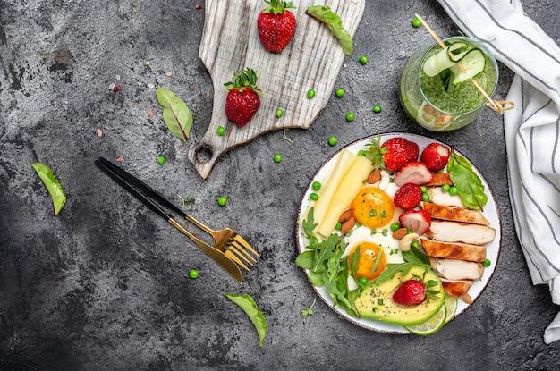 Filé de frango grelhado e abacate, ovos fritos com morango, queijo e nozes. dieta cetogênica. café da manhã com baixo teor de carboidratos e gordura. conceito de comida saudável, formato de banner longo. vista do topo,