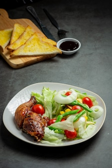 Filé de frango grelhado e vegetais em fundo escuro